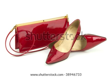 A pair of red patent leather high heel shoes with matching handbag on a white background