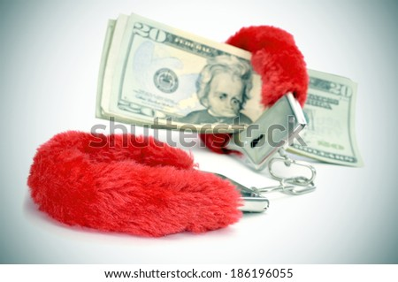 a pair of red sexy fluffy handcuffs and some dollar bills depicting the idea of paying for sex or the sex industry or the sex commerce - stock photo