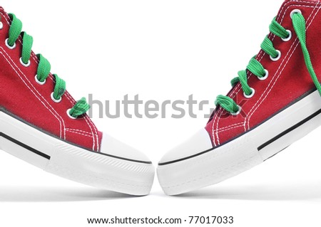 a pair of red sneakers with green shoelaces on a white background - stock photo