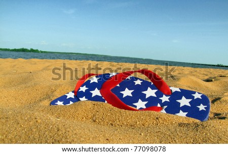 A pair of red, white, and blue flip flops with stars, on a sandy beach with water and sky in the background. - stock photo