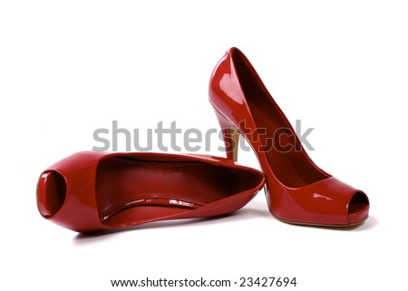 A pair of red women's high-heel shoes against white background, one shoe standing, one shoe lying - stock photo