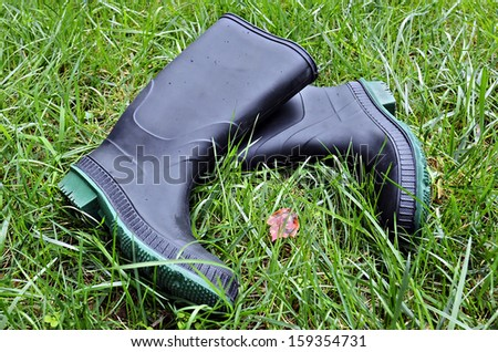 A pair of rubber boots in the grass with small rain drops on them. - stock photo
