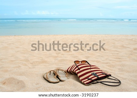 A pair of sandals and sunglasses on a sandy tropical beach