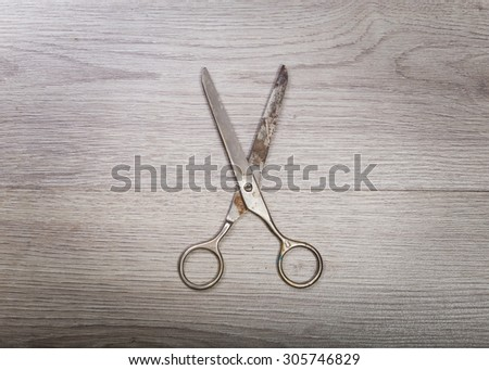 A pair of scissors sits half open on a worn butcher block counter top - stock photo