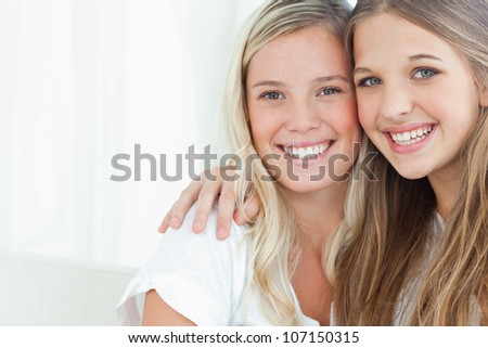 A pair of sisters smiling together as they look into the camera - stock photo