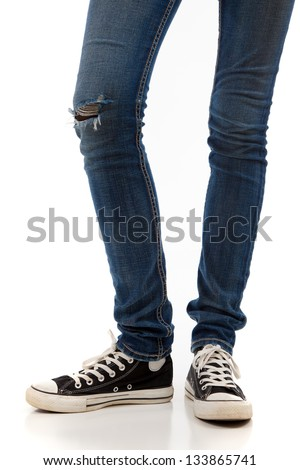 A pair of skinny legs in jeans and retro black sneakers on a white background - stock photo