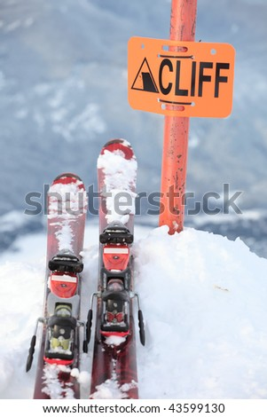 A pair of skis on the edge of a dangerous cliff in Whistler, British Columbia - stock photo