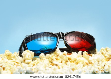 A pair of sleek 3D glasses rests on top of a pile of fresh popcorn. - stock photo