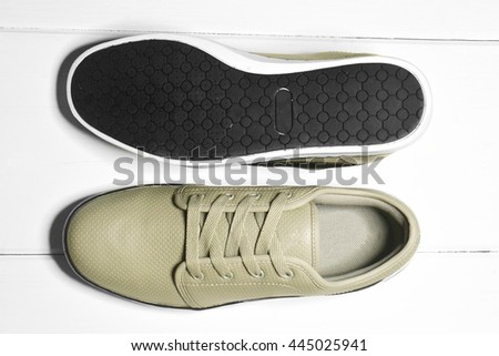 a pair of sneakers on a white wooden floor - stock photo