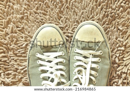 A pair of sneakers on beige carpet - stock photo
