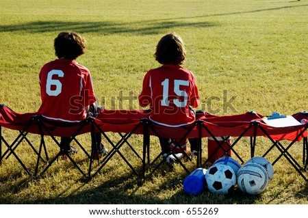 A pair of soccer players watch from the bench. - stock photo