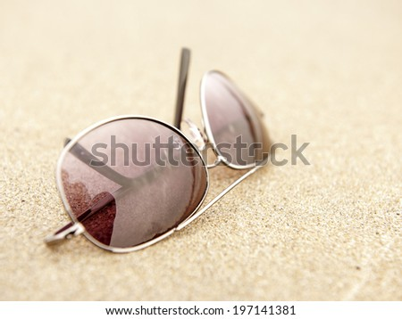 A pair of sunglasses laying on a granite counter top. - stock photo