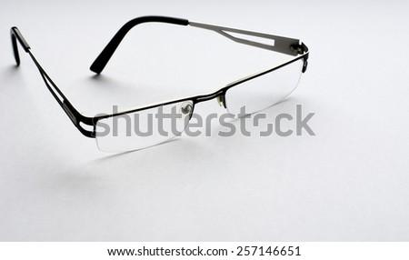 A pair of transparent glasses on white  paper background - stock photo