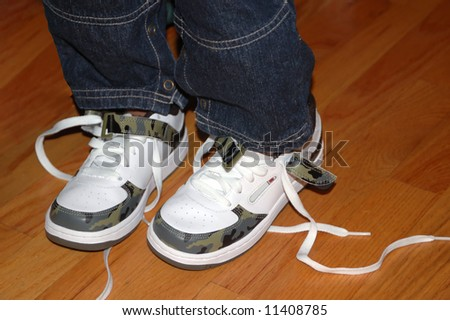 A pair of untied shoes on a toddler's legs - stock photo