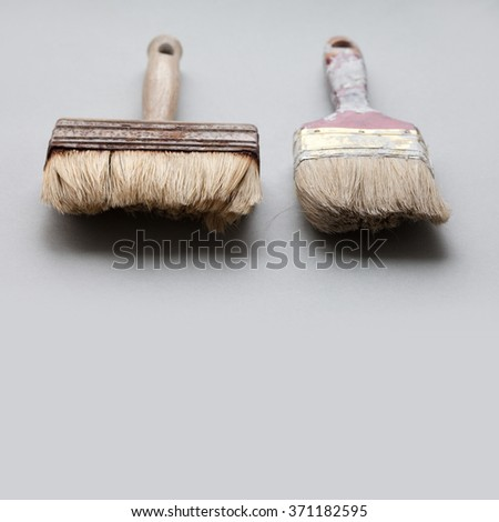 A pair of used, aged paintbrushes on gray background. Painter  brush texture, macro view, shallow depth of field photography. copy space - stock photo