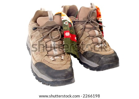 A pair of used hiking boots and socks over a white background - stock photo