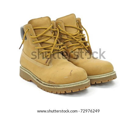 A pair of used work boots on a white background. - stock photo