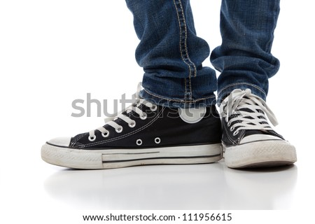 A pair of vintage looking, athletic shoes and skinny jeans on a white background with copy space - stock photo