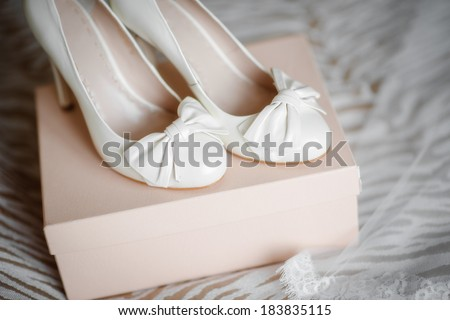 a pair of white elegant wedding shoes with bows - stock photo