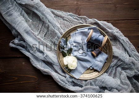 a pair of white gold rings lie on blue silk, wooden reel, all of this on a copper plate on a vintage wooden surface with blue gauze - stock photo