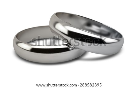 A pair of white gold wedding rings resting on an isolated white background - stock photo
