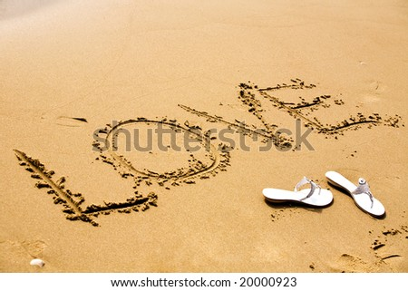 A pair of white sandals by inscription Love on a sand at sunny day