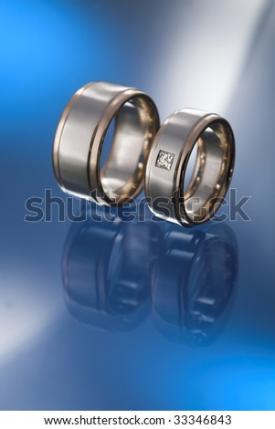 A pair of wide wedding bands by white and bronze gold, with diamond