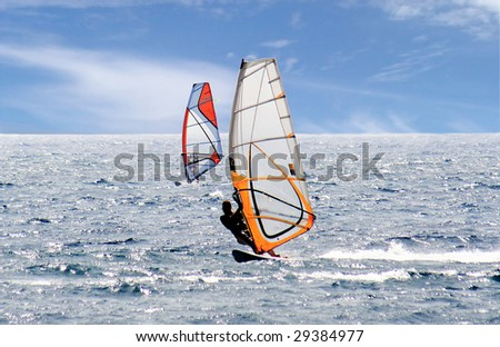 A pair of windsurfers on a highlighted sea with blue sky and wispy clouds - stock photo