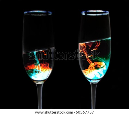 A pair of wine glasses with neon looking liquid inside