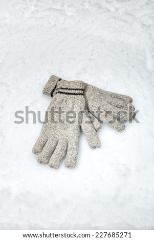 A pair of winter gloves lying in the snow - stock photo