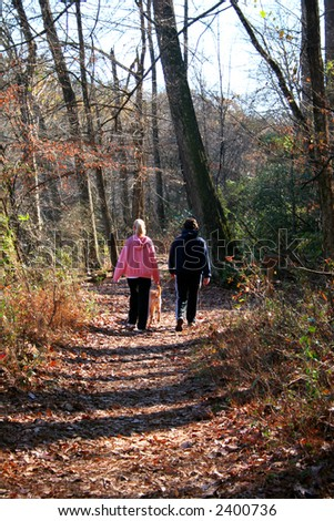A pair of women walking a dog down a forest path - stock photo