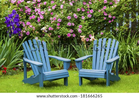 A pair of wooden Adirondack chairs in the summer garden. - stock photo