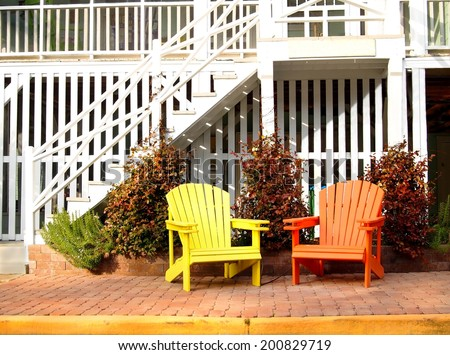 A pair of wooden adirondack chairs, one yellow and one orange, in front of a white beach house. - stock photo