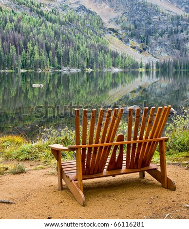 A pair of wooden Adirondack chairs placed on the shores of a calm wilderness lake - stock photo