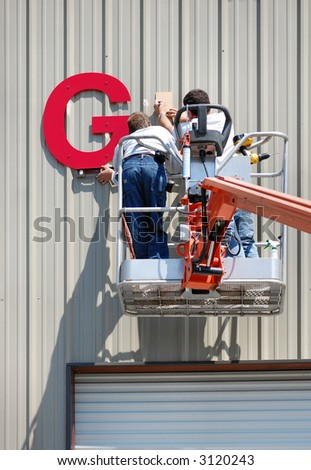 A pair of workmen install a sign on the side of an industrial building using a lift.