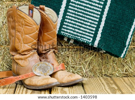 A pair of worn boots, belt and buckle, horse blanket and bale of hay are familiar sights around the Western tack room. - stock photo