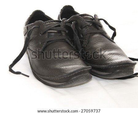 a pair of worn dark leather shoes with laces