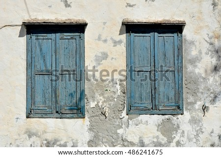 A pair of worn out blue window shutters