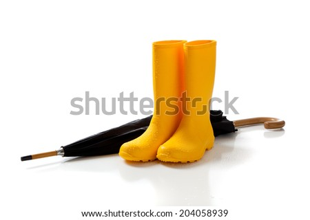 A pair of yellow rain boots and a black umbrella on a white background  - stock photo