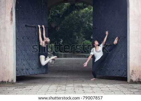 A pair of young ballet dancers performing in the outdoors