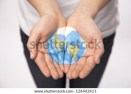A pair of young hands hold carefully to a painted world. - stock photo