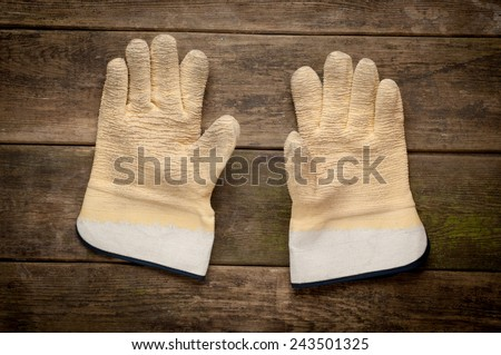 A pair work gloves lying on planks of wooden background  - stock photo