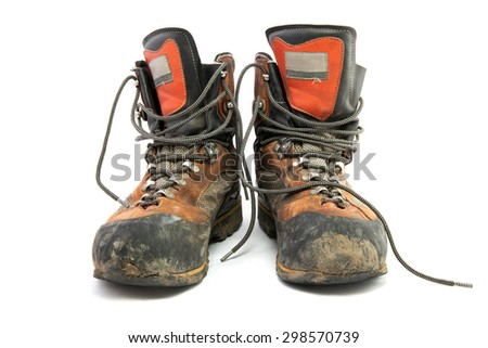 A pair worn hiking boots isolated on a white background. - stock photo