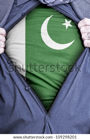 A Pakistani businessman rips open his shirt and shows how patriotic he is by revealing his countries flag beneath printed on a t-shirt - stock photo