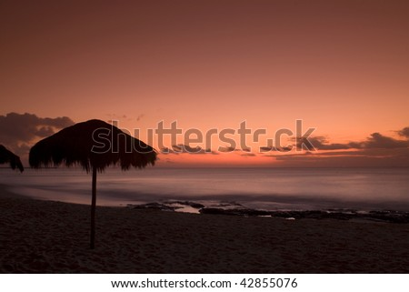 A palapa hut on the beach at sunset in Playa del Carmen Mexico - stock photo