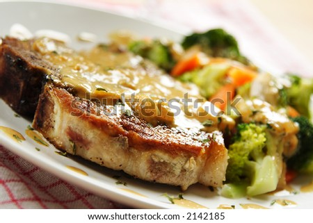 A pan fried pork chop with vegetables and coconut sauce