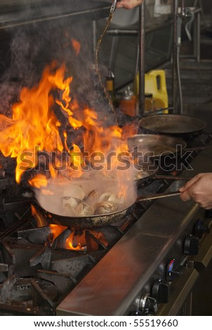 A pan in in a restaurant cooking with flames and smoke.