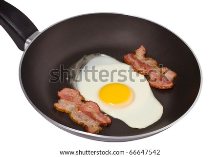 A pan with a fried egg and two pieces of bacon isolated - stock photo