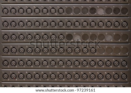 A panel with a plethora of XLR outlet connectors, shot head on. The XLR connector is a style of electrical connector, primarily found on professional audio, video, and stage lighting equipment. - stock photo