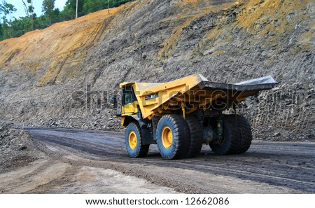 a panning shot a dump truck working on coal site - stock photo